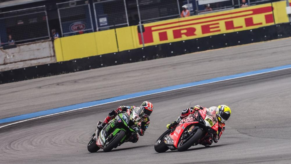 Alvaro Bautista and Jonathan Rea turning a corner on the racetrack as they are side by side on their bikes at the second Tissot Superpole Race | beIN SPORTS USA