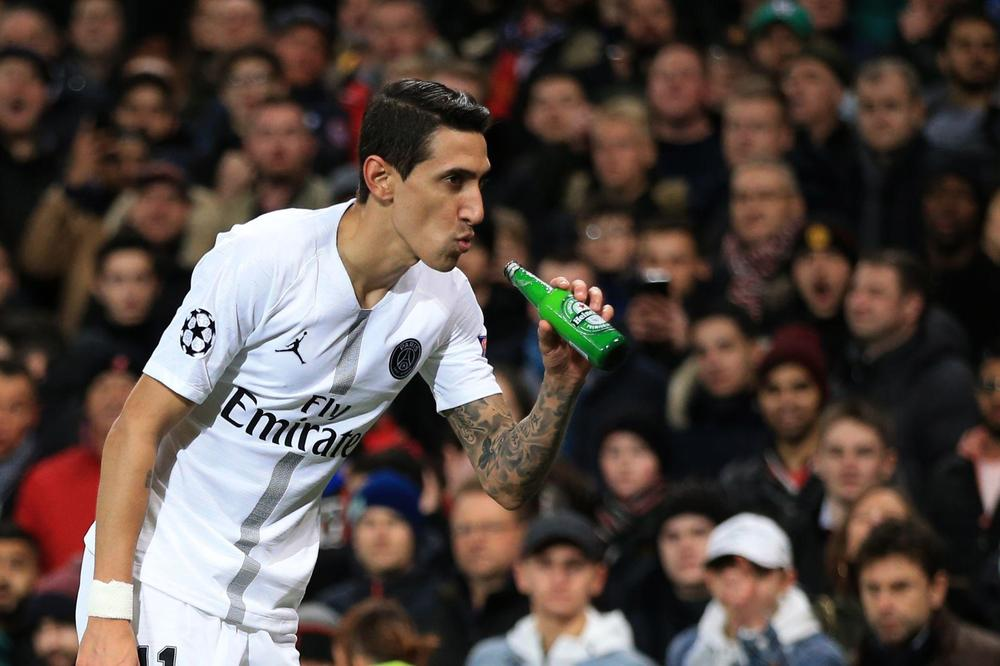 Angel Di Maria of Paris Saint-Germain makes to drink from a bottle of beer thrown onto the pitch during the UEFA Champions League Round of 16 First Leg match between Manchester United and Paris Saint-Germain at Old Trafford
