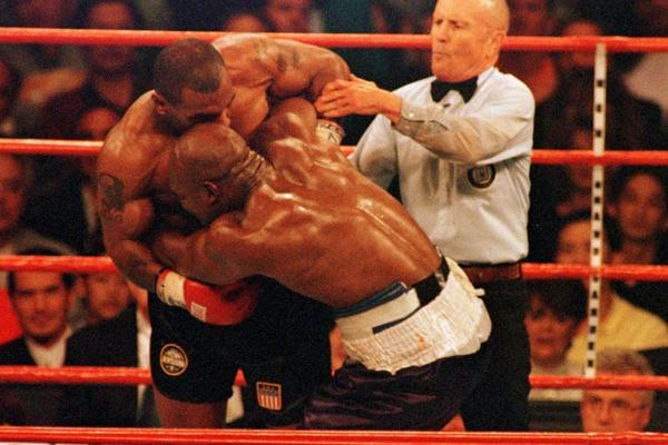 Referee Mills Lane steps as Mike Tyson bites Evander Holyfield's right ear during the WBA World Heavyweight title fight in 1997 - beIN SPORTS