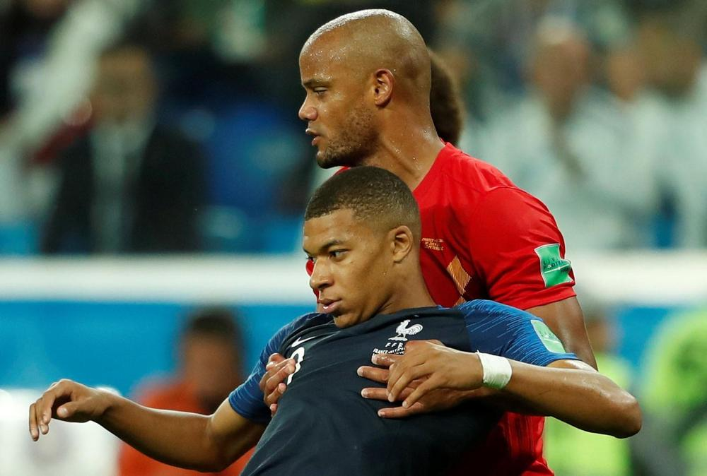 Kylian Mbappe of France is held up by Vincent Kompany of Belgium during the semi-final World Cup clash between the two nations.