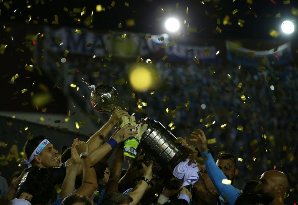 Players of Gremio celebrate with the trophy. REUTERS/Agustin Marcarian