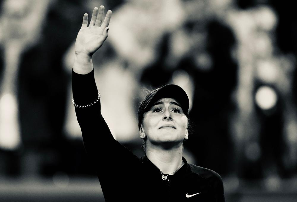 """A black and white shot of Bianca """"Bibi"""" Andreescu as she looks up and waves to the crowd after defeating Elina Svitolina at Indian Wells 