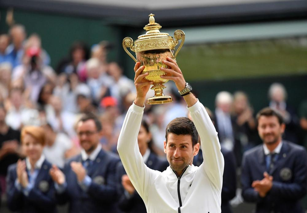Serbia's Novak Djokovic poses with the trophy as he celebrates winning the final against Switzerland's Roger Federer, July 14, 2019