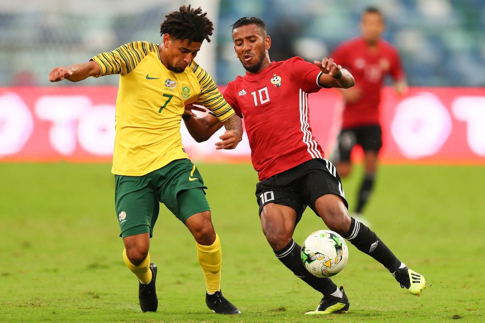 South Africa's midfielder Keagan Dolly (L) vies for the ball with Libya's forward Hamdou Elhouni (R) during the 2019 Africa Cup of Nations qualifier match between South Africa and Libya, on September 8, 2018 in Durban, South Africa.